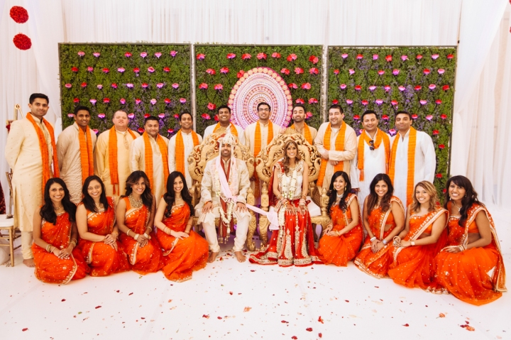 Bridal party at an Indian wedding posing for a photo with the bride and groom in the mandap.
