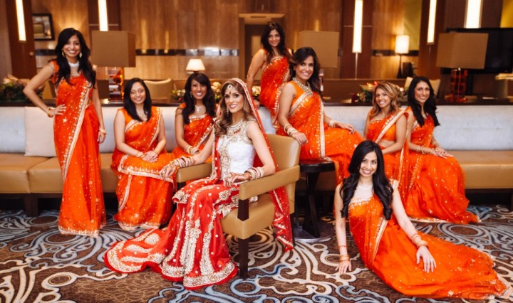 An Indian bride dressed up for her Hindu wedding ceremony surrounded by her bridesmaids wearing red saris.
