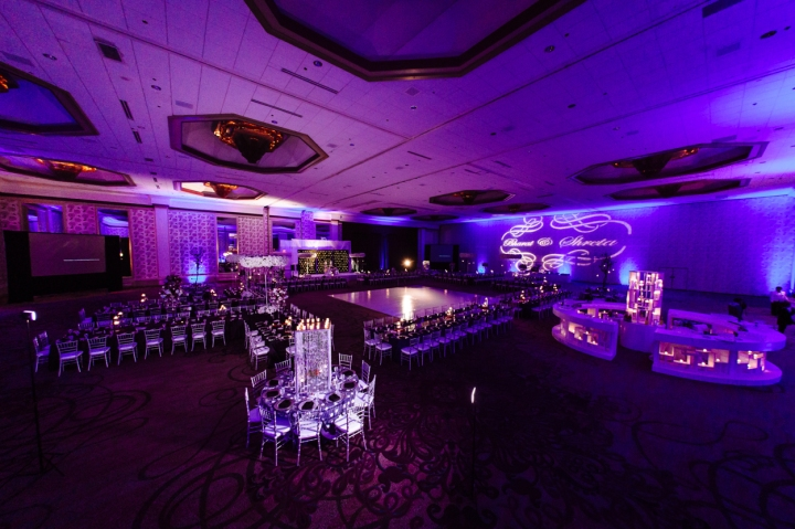 The ballroom with purple lighting, setup for an Indian wedding reception.