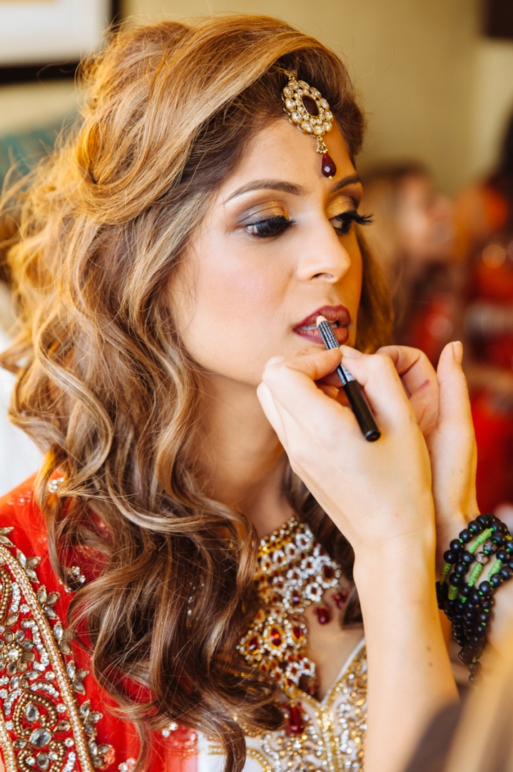 An Indian bride wearing a red and gold lehenga and a tikka on her forehead, having her makeup done for her Indian, Hindu, wedding ceremony.