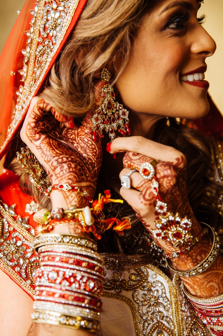 An Indian bride putting on her beautiful red and gold earrings for her Hindu wedding ceremony.