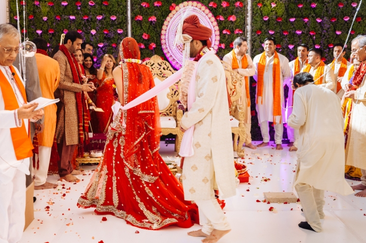 An Indian bride sitting in a chair and her groom taking pheres their Hindu wedding ceremony.