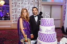 An Indian bride and groom posing for a photo before cutting their wedding cake during their reception.