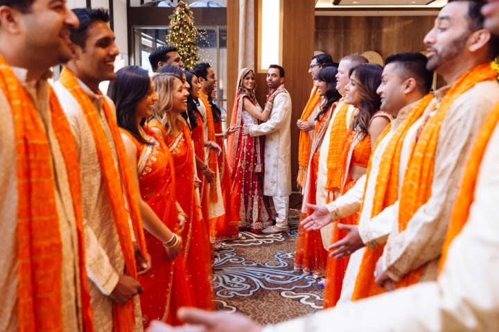 An Indian bride and groom taking fun photos with their bridal party before their wedding.