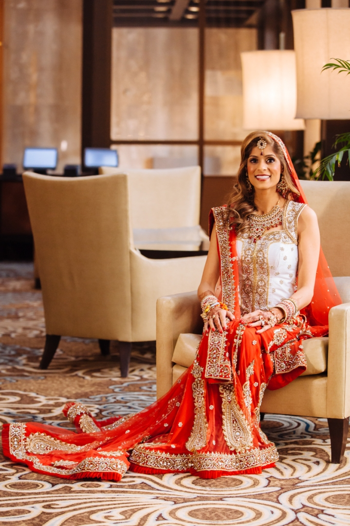 An Indian bride wearing a red and gold lehenga posing for a photo before her wedding starts.