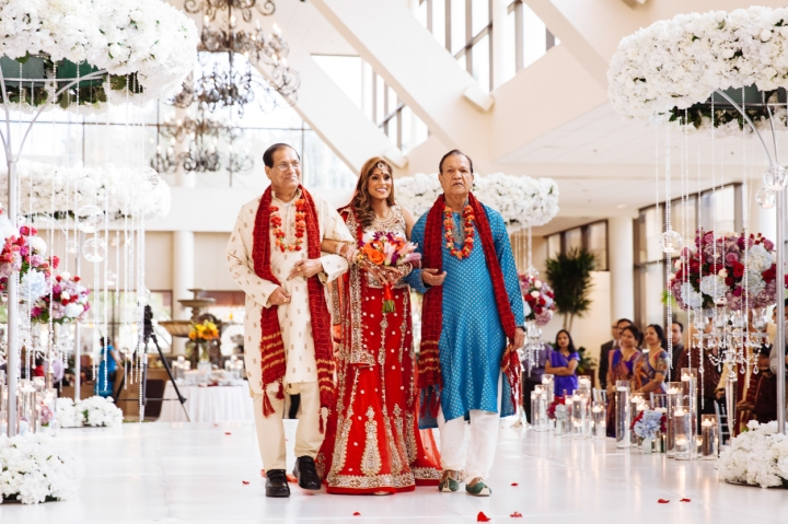 An Indian bride wearing a red and gold lehenga walking down the aisle with her uncles.