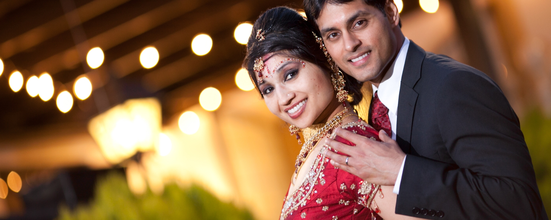 Lovely photo of an Indian bride and groom posing for a photo during their Indian wedding reception.