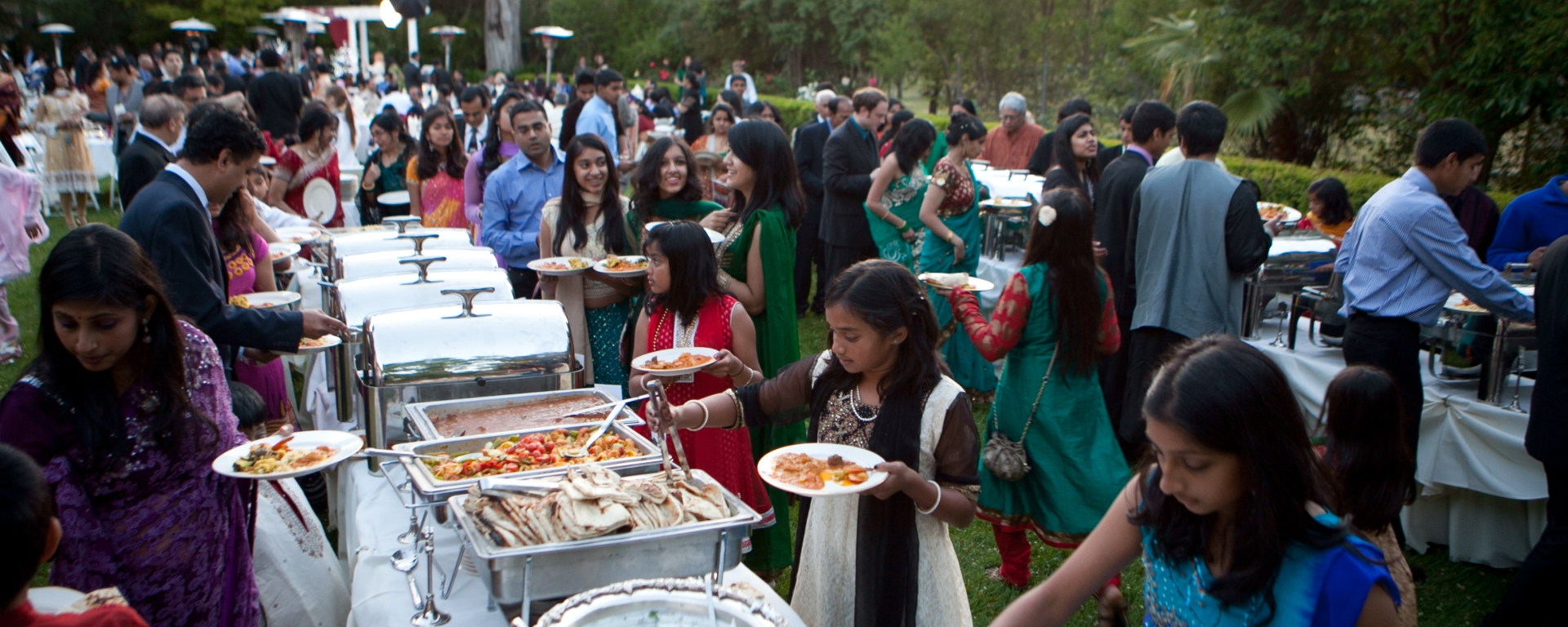 Guests getting dinner in the buffet line at an outdoor Indian wedding reception.