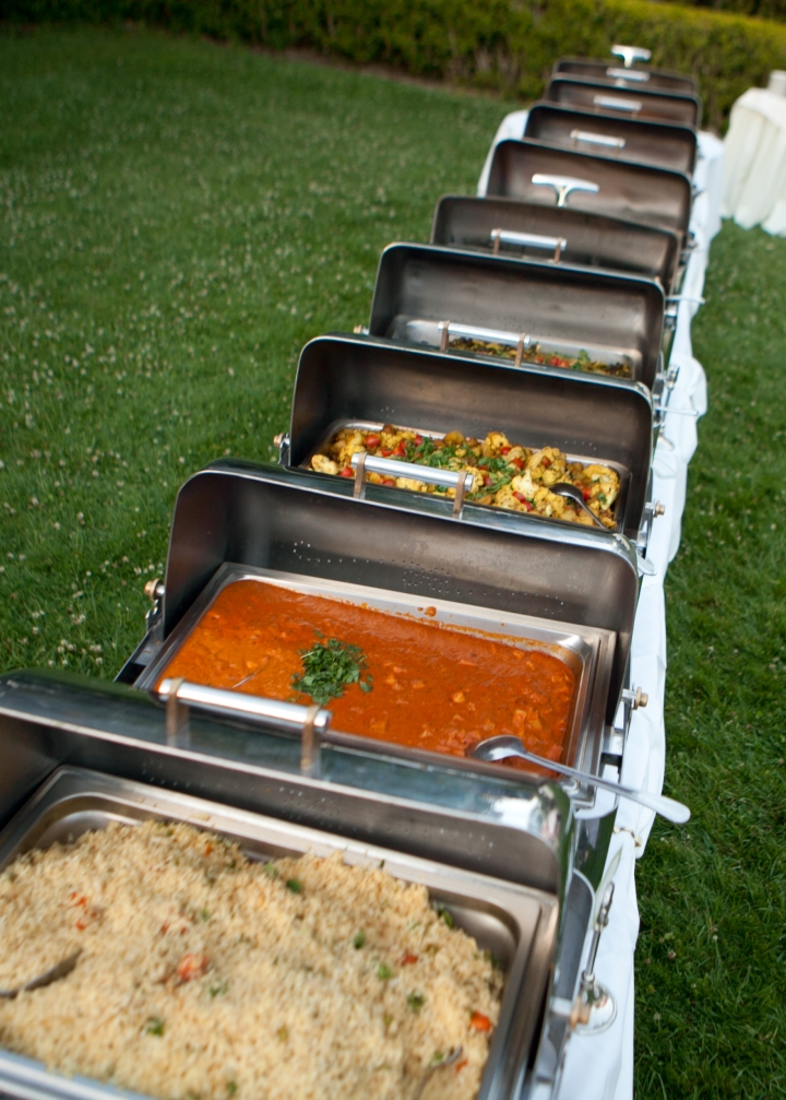 Indian food in chafing dishes setup for for an Indian wedding reception.