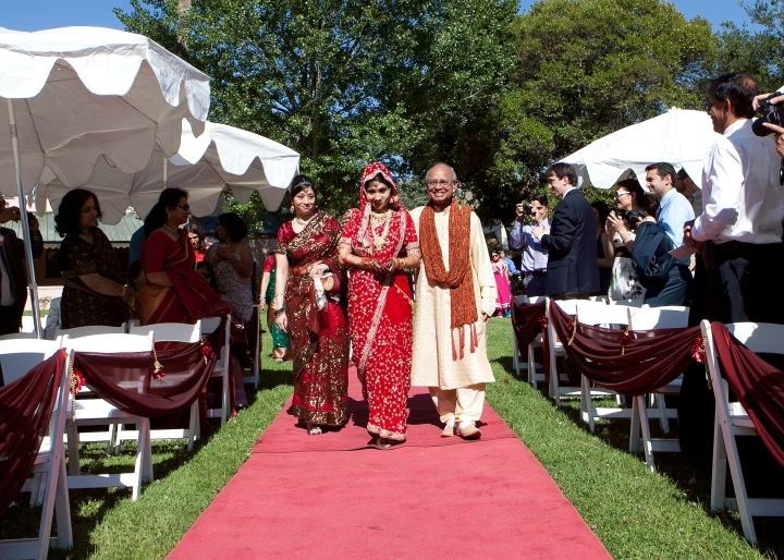 A Bengali, Indian bride walking down red carpet aisle with her father and sister.