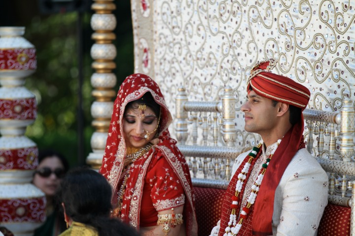 Indian bride with her hed covered by her dupatta sitting in the mandap
