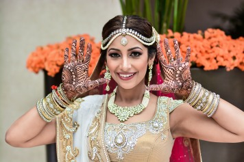 Indian bride holding her hands up, showing her mehndi on her wedding day