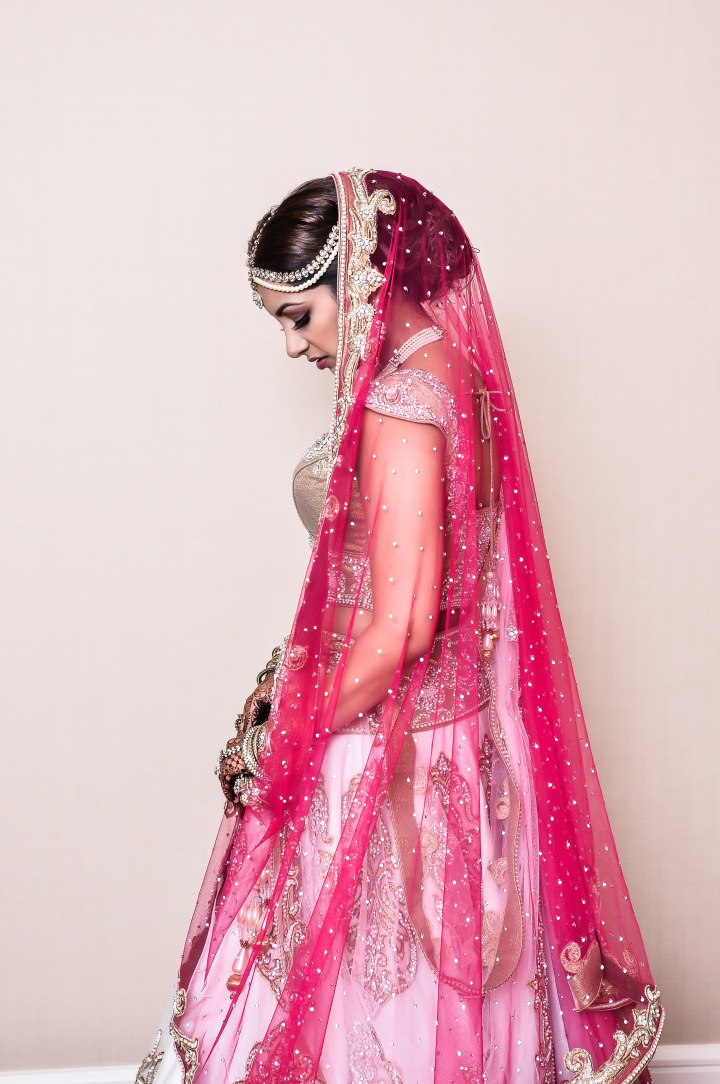 Indian bride's pink dupatta with white and gold lehenga