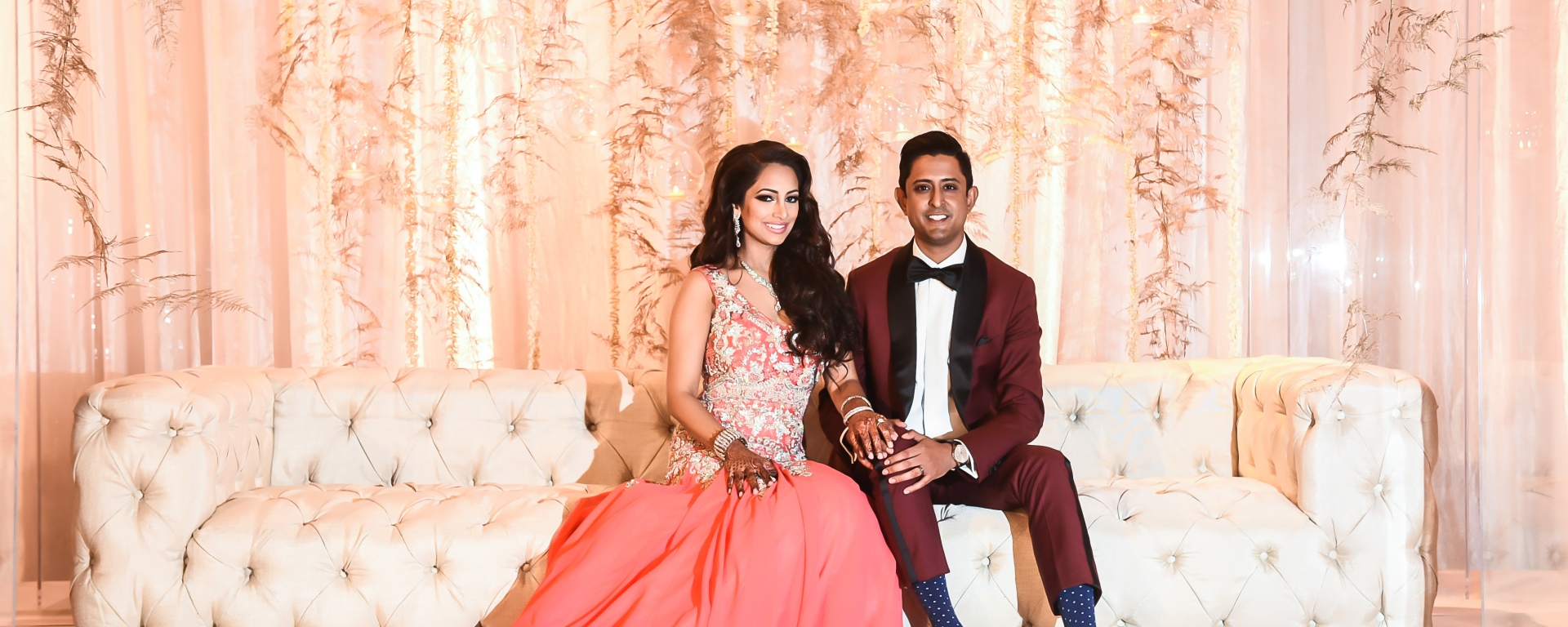 Indian bride wearing her coral-pink reception gown, sitting on the sweetheart stage with her husband.