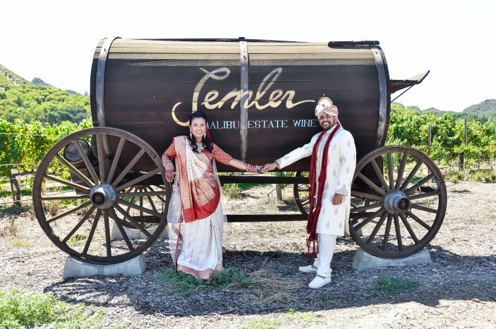 Indian bride and groom during their pre wedding photoshoot, standing in front of a barrel.