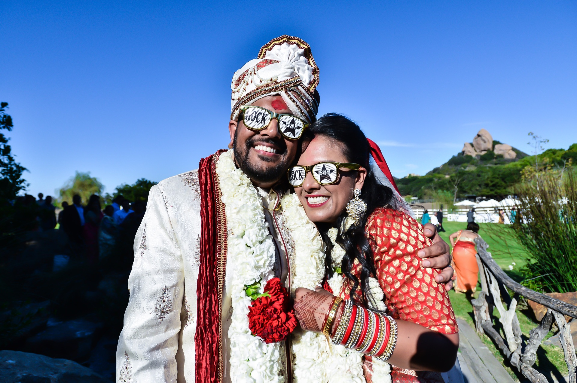 Indian bride and groom wearing funny sunglasses, happily posing for the camera at their Hindu wedding