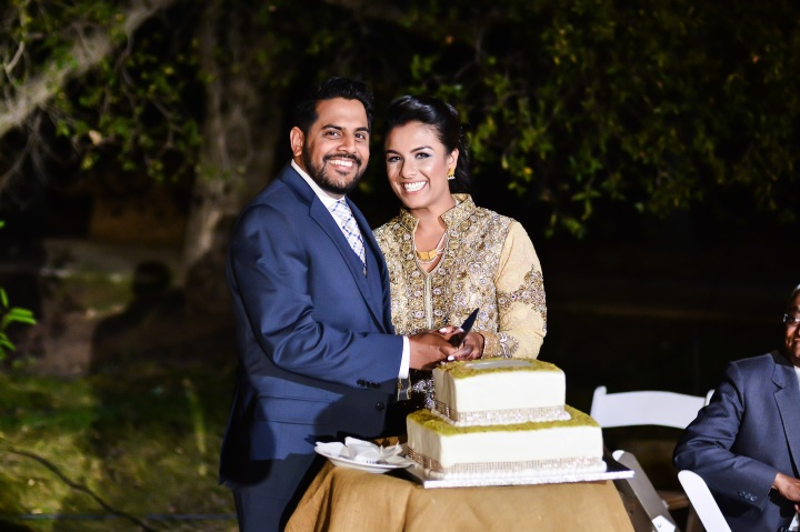 Indian bride and groom cutting the cake at their wedding reception