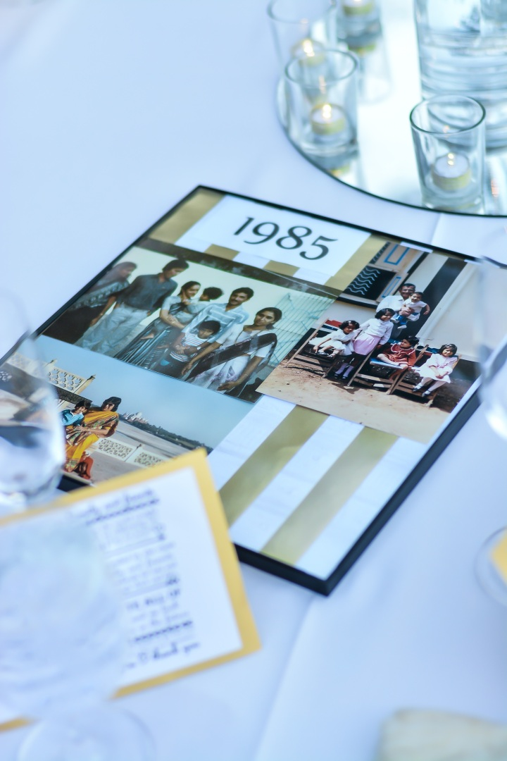 personalized table numbers with photos and years of significance at an Indian wedding reception