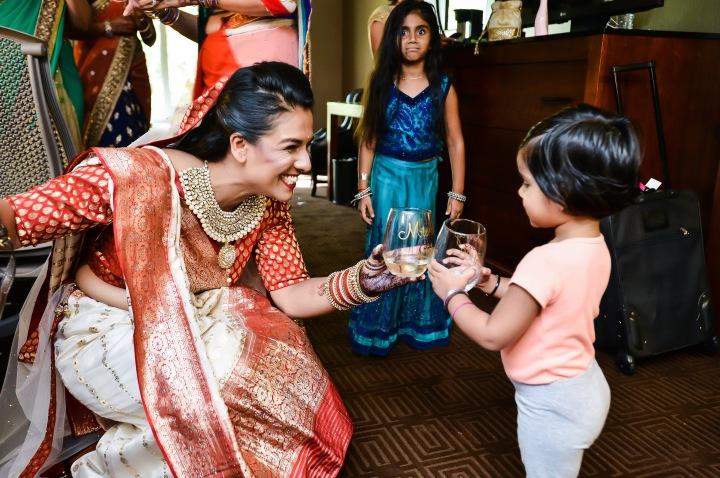 Rakhee-Amrish-gift-exchange-Indian-wedding-venue-photography-Greycard-Hindu-outdoor-dresses-bride-with-child