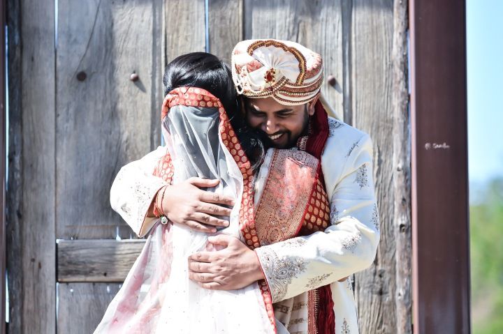 Bride and groom embracing during their first look at an Indian wedding in Malibu