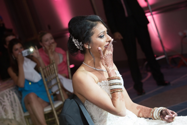 Indian bride wearing white gown with a surprised expression.