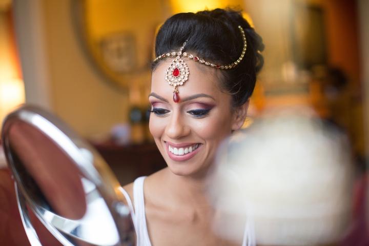 Indian bride smiling, wearing her tikka