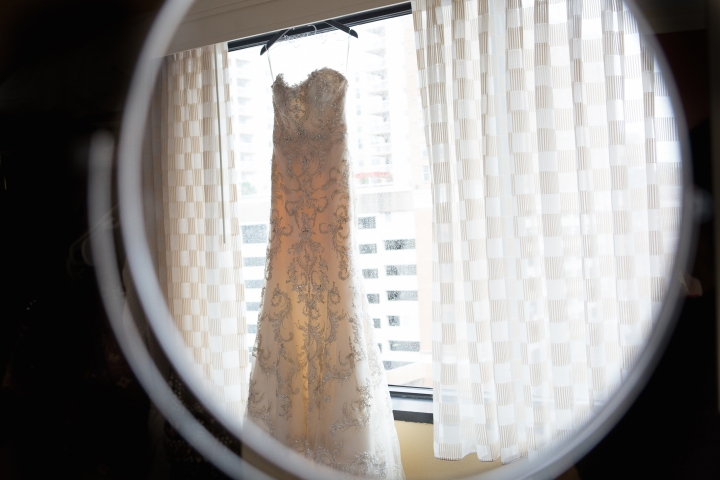 white wedding gown hanging with a window in the background