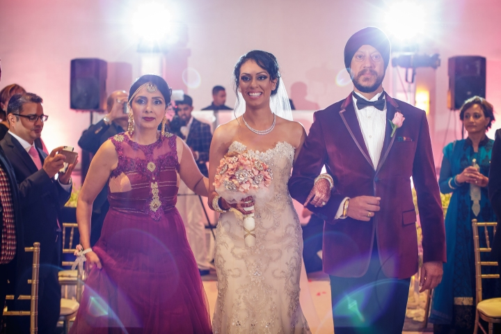 Sikh bride wearing a white wedding gown escorted down the aisle by her parents