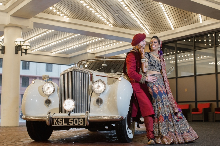 Sikh bride and her Canadian groom leaning against a classic car wearing their Indian wedding clothes