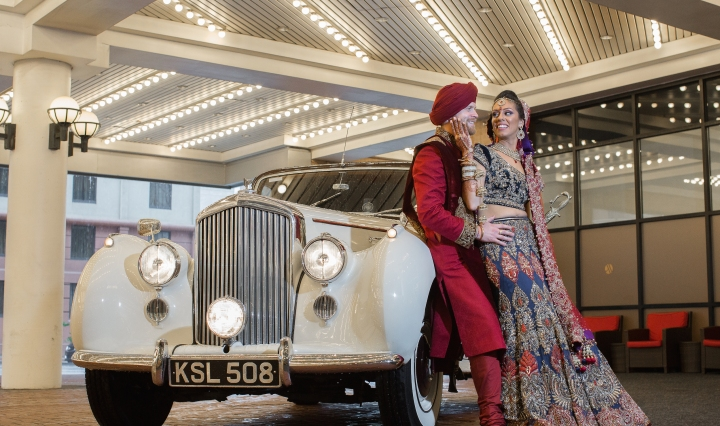 Indian bride and Canadian groom leaning against a classic car
