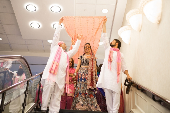 Sikh ride escorted by her male cousins, holding a decorative clloth over her head walking her to her Anand Karaj.