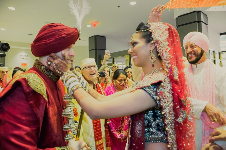 Indian bride and groom at their Anand Karaj. The bride with her hands n her husband's face.