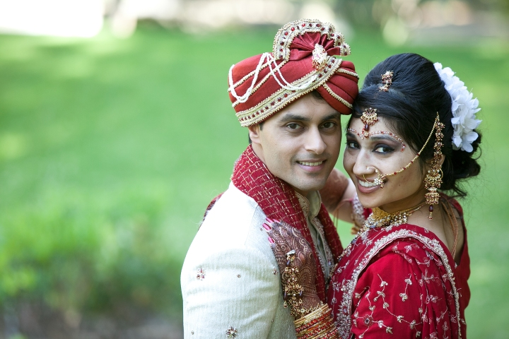 Indian bride and groom posing for a photo at their Indian wedding-both are smiling at the camera