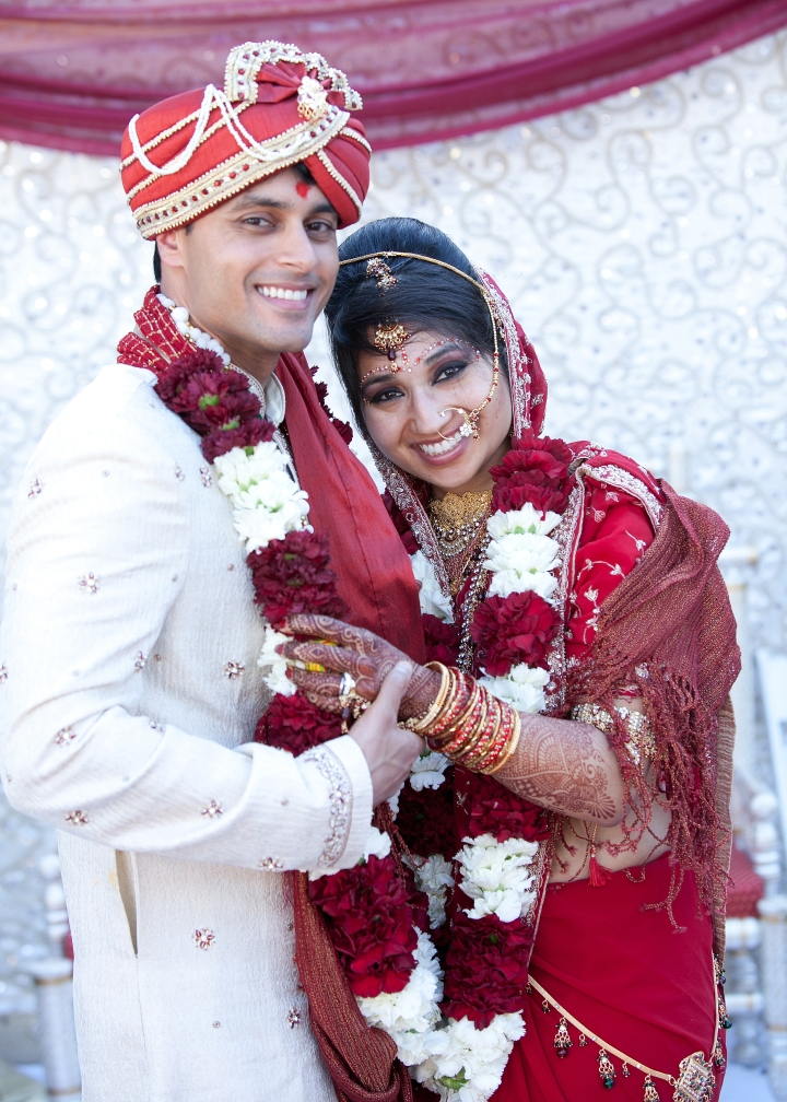 Indian bride and groom wearing their traditional wedding clothes, holding each other and smiling at the camera