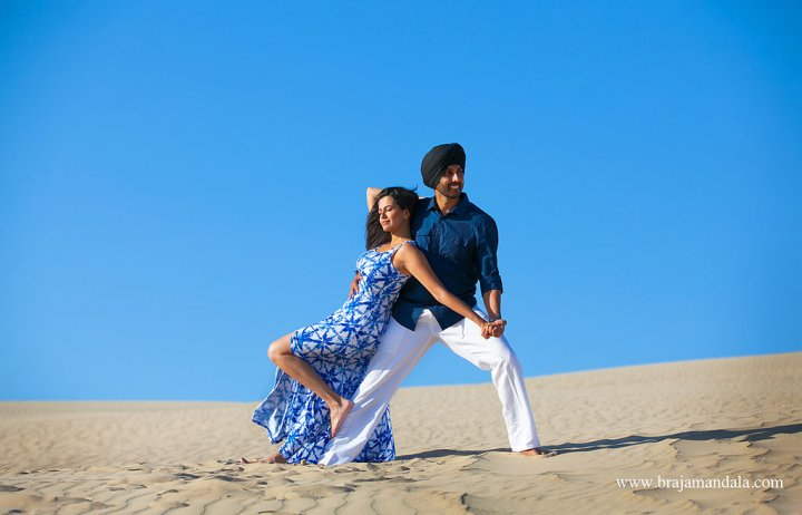 Indian bride and groom leaning in a pose on the beach - in the sand