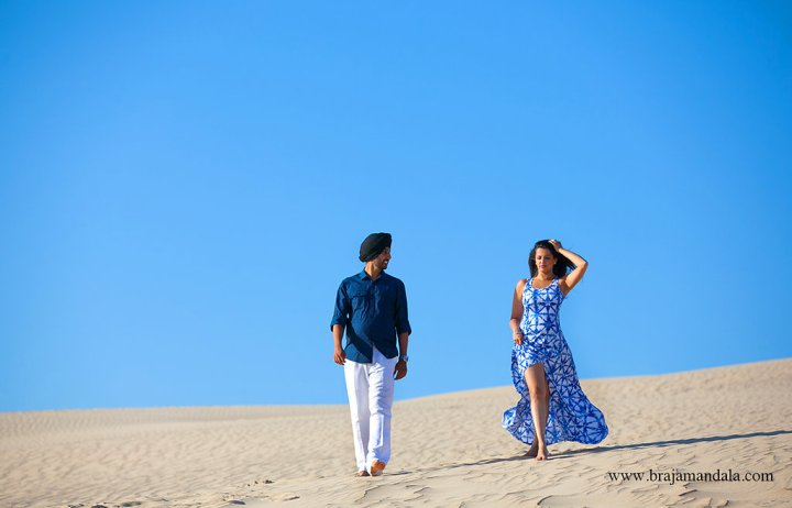 Indian bride and groom dressed in blue walking in the sand