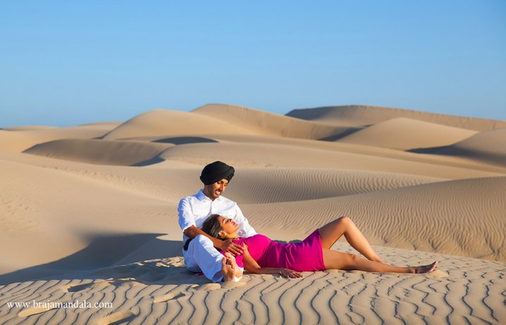 Indian bride wearing pink dress with laying down in the sand with her head in her fiances lap.