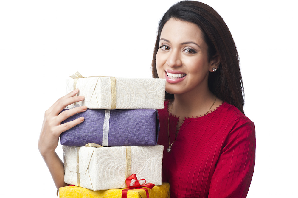 Indian woman holding boxes of wrapped gifts